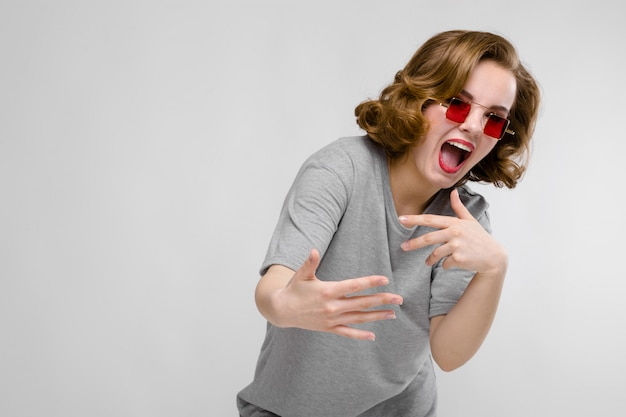 Encantadora joven en una camiseta gris sobre un fondo gris. chica con gafas rojas de ojos cuadrados. la chica se inclinó hacia adelante Foto Premium
