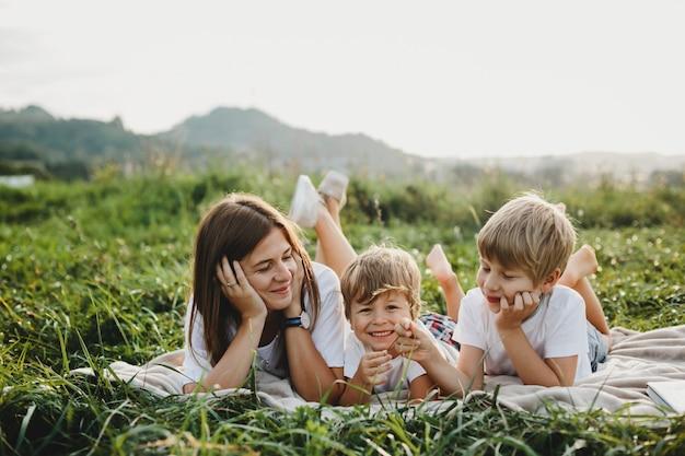 Encantadora joven madre se divierte con sus pequeños hijos mintiendo Foto gratis