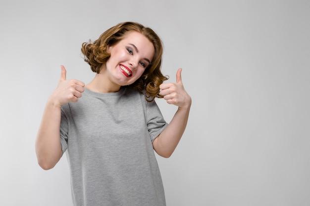 Encantadora jovencita con una camiseta gris. chica mostrando signos de clase Foto Premium