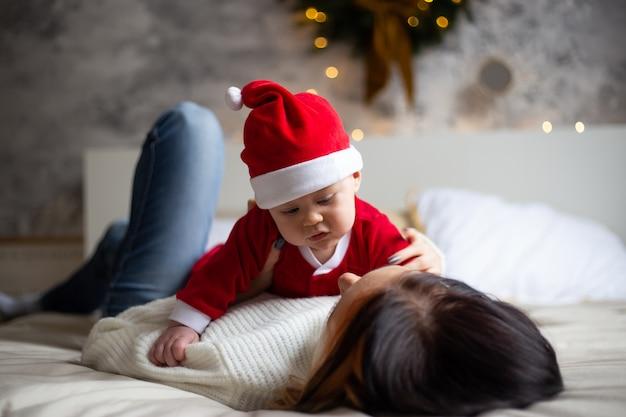 Encantadora madre mira a su pequeño hijo pequeño y sonriendo en el fondo de árboles de navidad y guirnaldas en la casa Foto Premium