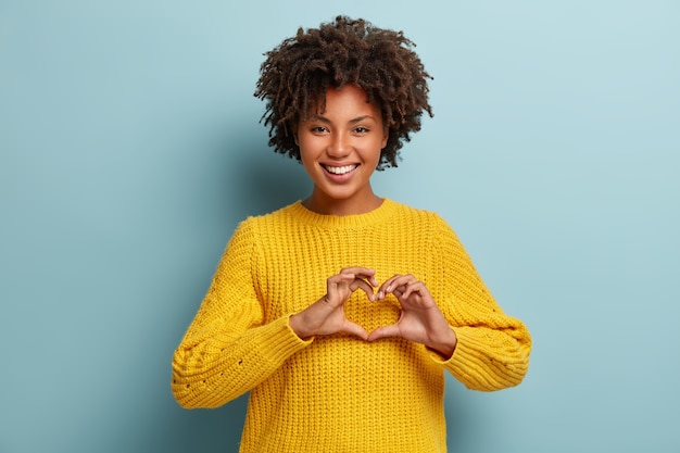 Encantadora mujer con un afro posando con un suéter rosa Foto gratis