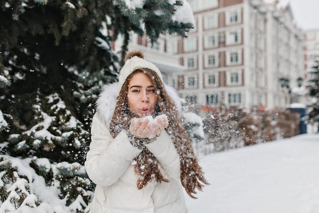 Encantadora mujer alegre que sopla copos de nieve de sus manos en día de invierno al aire libre en la calle. Foto gratis