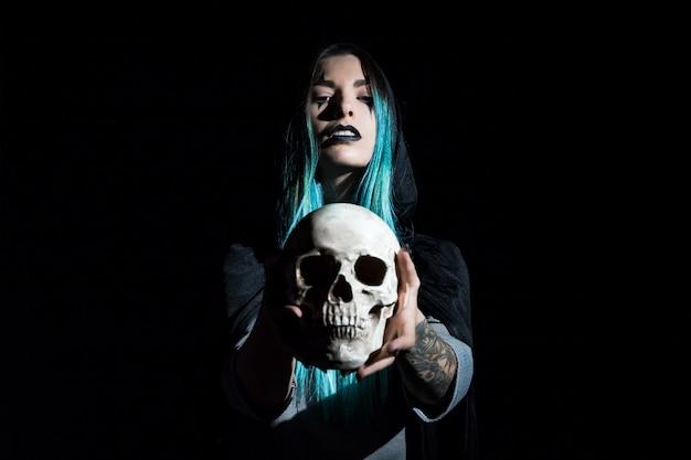 Encantadora mujer con cráneo humano Foto gratis