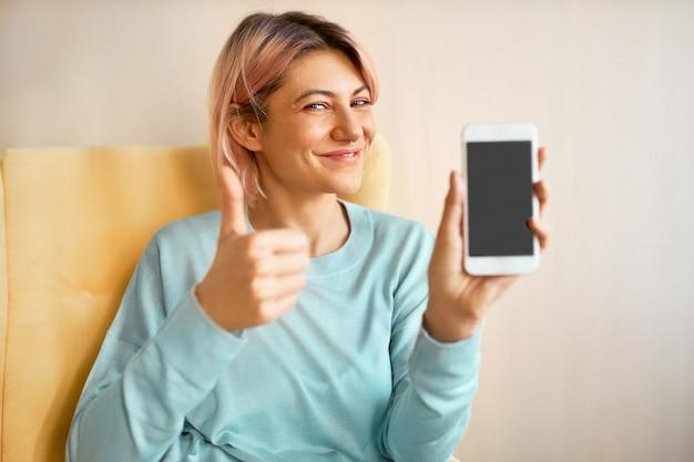 Encantadora mujer joven feliz con cabello rosado sosteniendo un teléfono inteligente con pantalla negra en blanco con espacio de copia para su contenido publicitario, haciendo gesto de pulgar hacia arriba como señal de aprobación, guiñando un ojo a la cámara Foto gratis