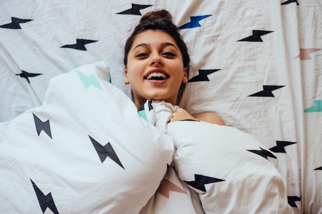 Encantadora mujer joven yace en la cama, cubierta con una manta Foto gratis