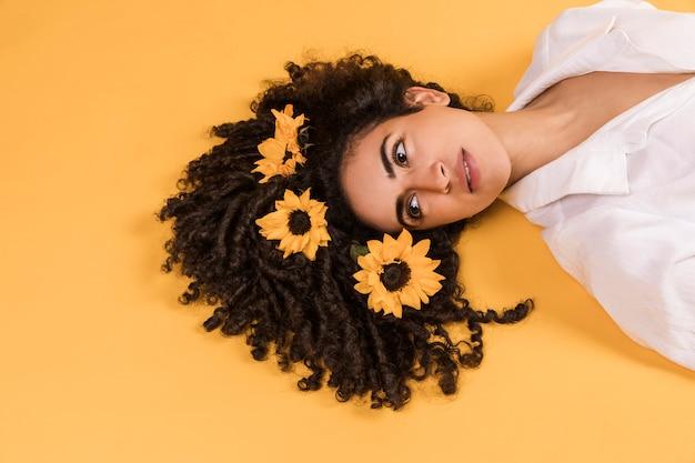 Encantadora mujer pensativa con flores en el pelo Foto gratis