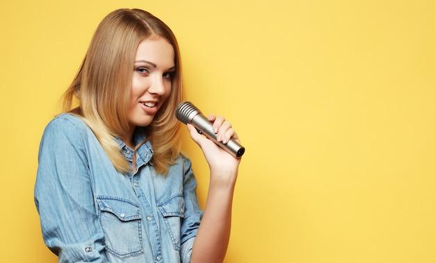 Encantadora mujer rubia cantando con micrófono en estudio sobre yel Foto Premium
