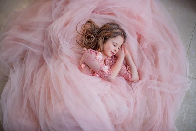Encantadora niña en vestido rosa se ve preciosa mientras duerme en el piso Foto gratis
