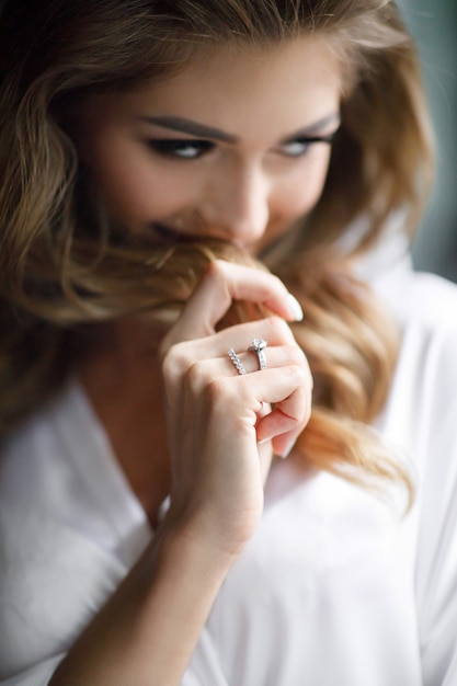Encantadora novia rubia con rizos y piel brillante posa en bata de seda blanca en la habitación Foto gratis