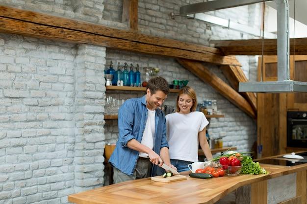 Encantadora pareja alegre que cocina la cena juntos y se divierte en la cocina rústica Foto Premium