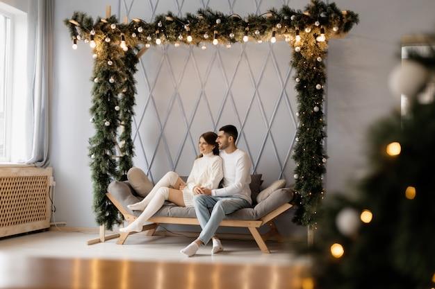 Encantadora pareja joven en ropa de hogar blanca acogedora posa en una habitación con árbol de navidad Foto gratis