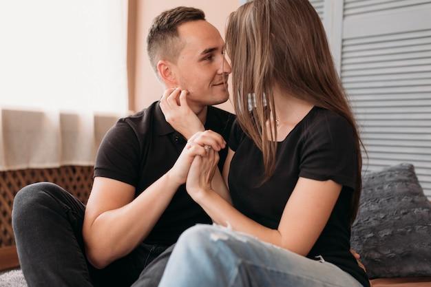 Encantadora pareja joven vestida en estilo casual se sienta en el piso Foto gratis