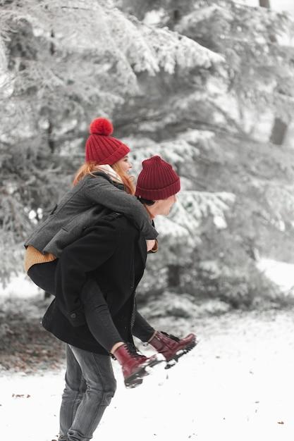 Encantadora pareja jugando en la nieve de lado Foto gratis