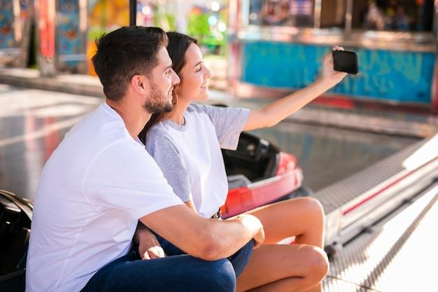 Encantadora pareja tomando selfie en feria Foto gratis