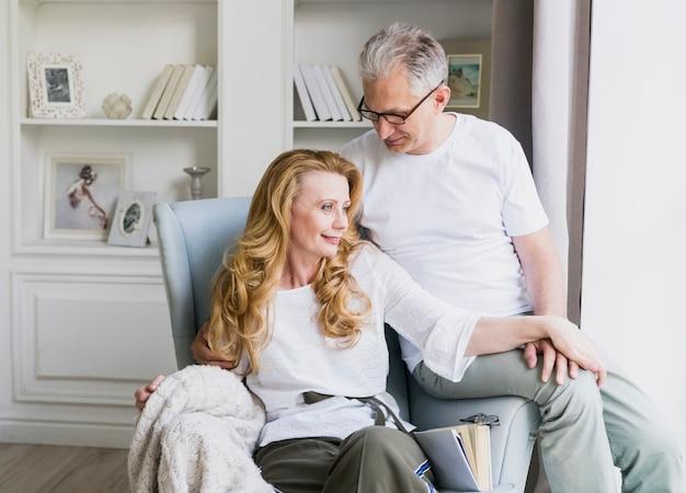 Encantadora senior hombre y mujer en sillón Foto gratis