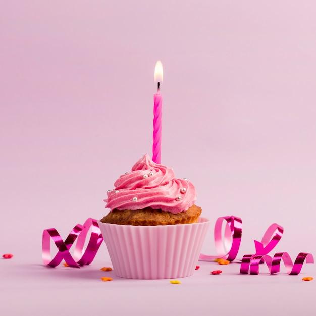 Encendiendo velas sobre los muffins con chispas y serpentinas sobre fondo rosa Foto gratis