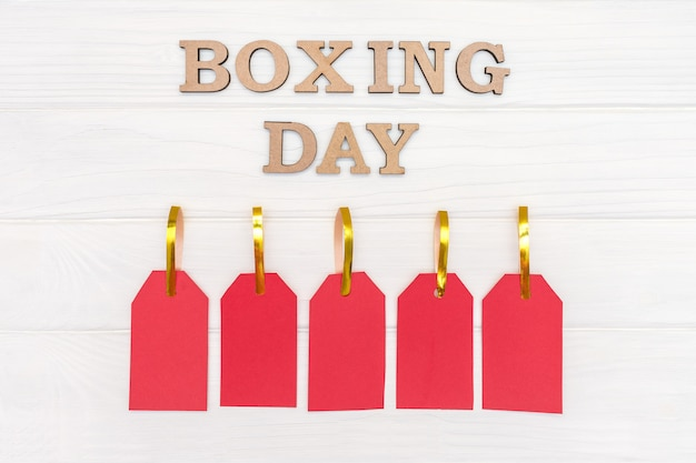 Por encima de las palabras boxeing day y cinco etiquetas rojas sobre fondo blanco de madera Foto Premium