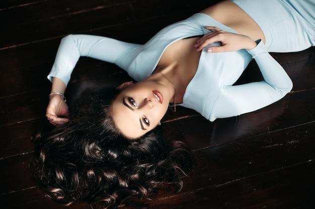 Por encima de la vista de la hermosa mujer en vestido azul acostado en el piso de madera oscura. Foto Premium