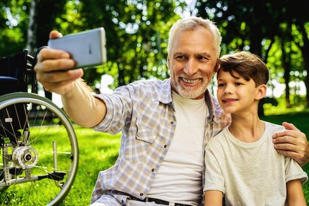 Encuentro familiar en el parque. chico y abuelo selfie. Foto Premium