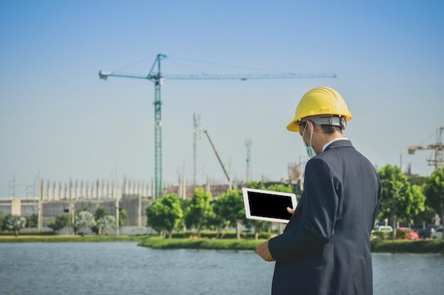 Encuesta de hombre asiático o empresario en la construcción de bienes raíces del sitio Foto Premium