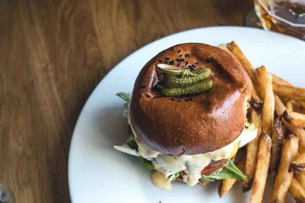 Encurtidos pequeños en la parte superior de una hamburguesa de ternera apetitosa con papas fritas Foto gratis