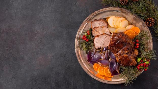Endecha plana de bistec de navidad en un plato con decoración de piñas y espacio de copia Foto gratis