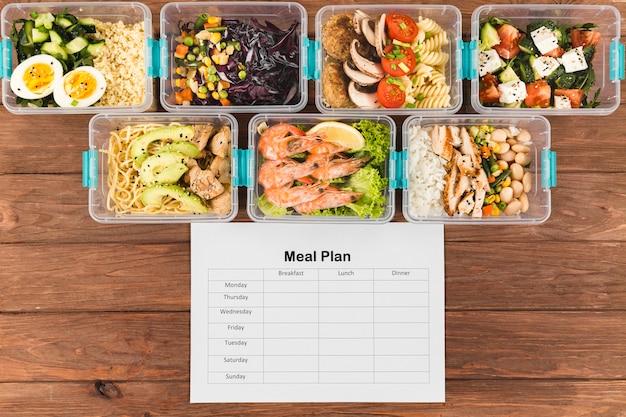 Endecha plana de cacerolas de plástico con comida y plan de comidas. Foto gratis