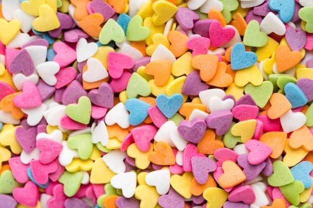 Endecha plana de coloridos dulces en forma de corazón Foto gratis