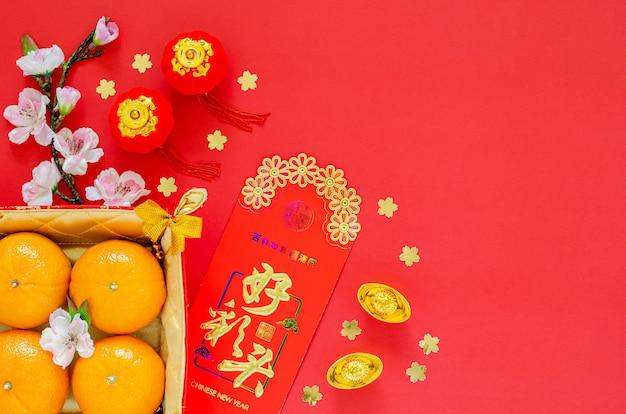Endecha plana de decoración del festival del año nuevo chino sobre fondo rojo. el idioma chino en lingote significa bendición, en paquete rojo de dinero significa
