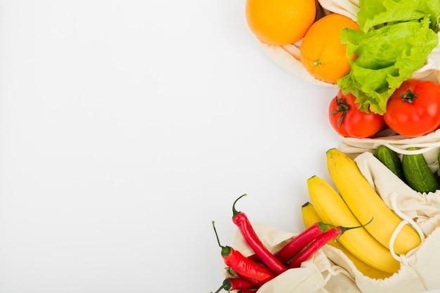 Endecha plana de frutas y verduras en bolsas reutilizables con espacio de copia Foto gratis