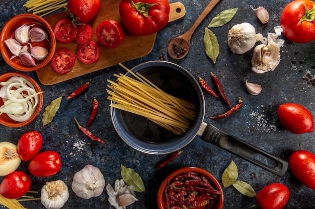 Endecha plana de pasta en una sartén con tomates y verduras Foto gratis