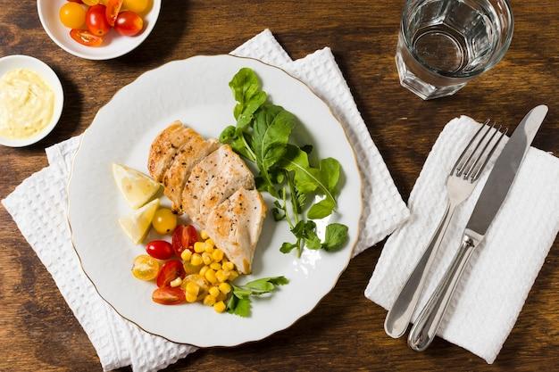 Endecha plana de pechuga de pollo con surtido de verduras Foto gratis