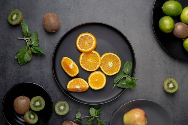 Endecha plana de rodajas de mandarina en un plato con kiwi Foto gratis