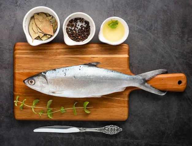 Endecha plana sabroso pescado en tabla de cortar Foto gratis