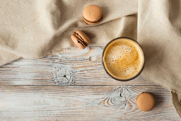 Endecha plana de taza de café y macarons Foto gratis