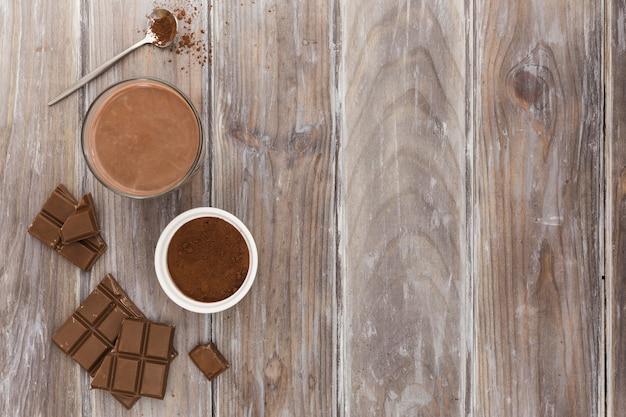Endecha plana de taza de chocolate caliente con cacao en polvo Foto gratis