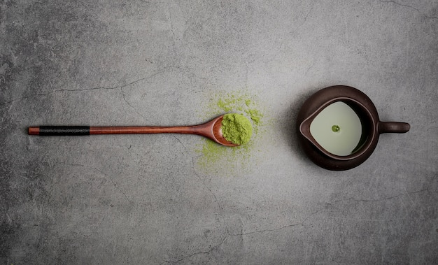 Endecha plana de té matcha con cuchara de madera Foto gratis
