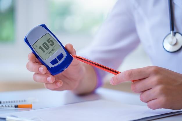 El endocrinólogo muestra un medidor de glucosa con nivel de glucosa en sangre al paciente con diabetes durante la consulta médica y el examen en el hospital. estilo de vida diabético y asistencia sanitaria Foto Premium