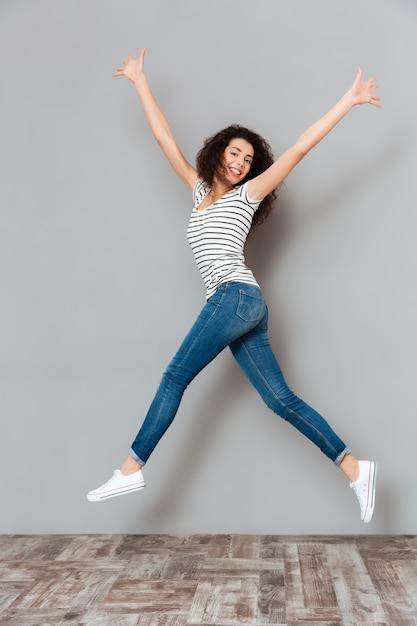 Enérgica mujer de 20 años en camiseta a rayas y jeans saltando con las manos vomitando en el aire sobre gris Foto gratis