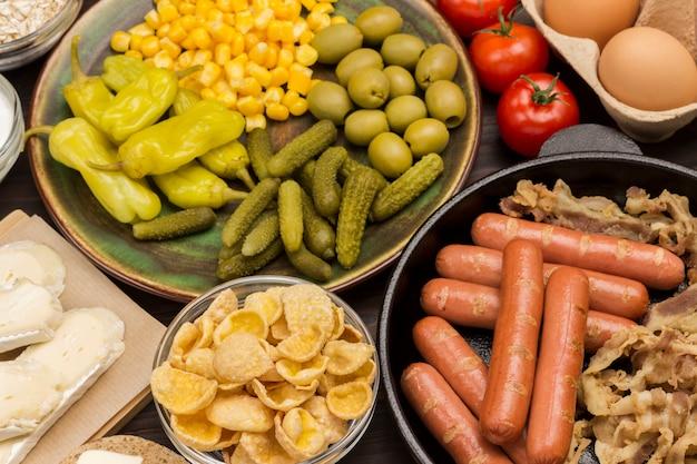 Energy breakfast food set: conservas de pepinos, maíz, pimiento en plato de cerámica. salchichas en sartén. garbanzos, aceitunas, tomates. Foto Premium