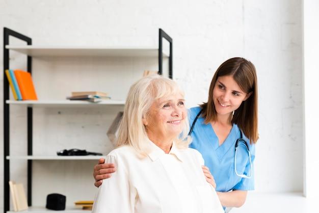 Enfermera y anciana mirando por la ventana Foto gratis