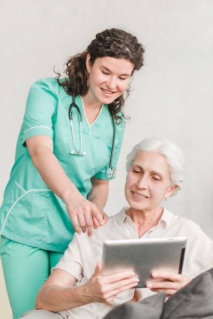 Enfermera apuntando a la pantalla mostrando algo a su paciente en tableta digital Foto gratis