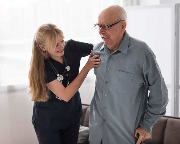 Enfermera ayudando a anciano a levantarse Foto gratis