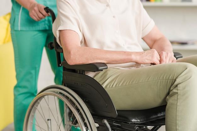 Enfermera ayudando a su paciente sentado en silla de ruedas Foto gratis