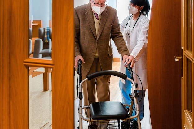 Enfermera en bata blanca sosteniendo la mano de un anciano con un andador en el interior Foto Premium
