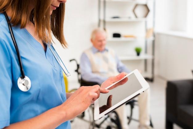 Enfermera comprobando su tableta cerca Foto gratis