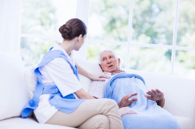 Enfermera cuidando paciente anciano enfermo en casa Foto Premium