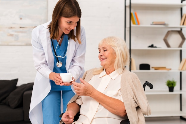 Enfermera dando té a la anciana Foto gratis