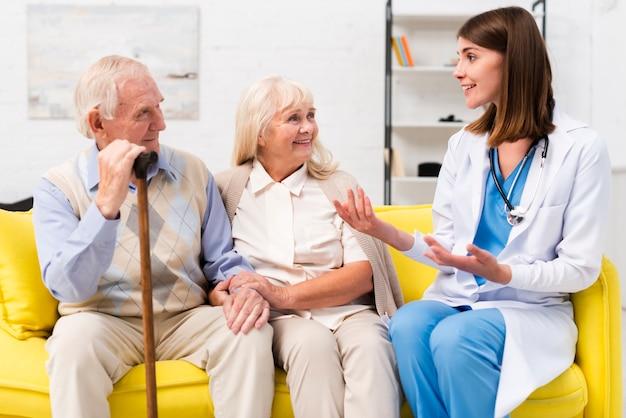 Enfermera hablando con anciano y mujer Foto gratis