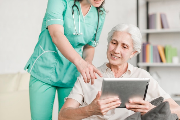 Enfermera mostrando algo al paciente femenino senior en tableta digital Foto gratis
